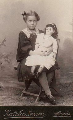 Seated girl with large doll in white dress.
