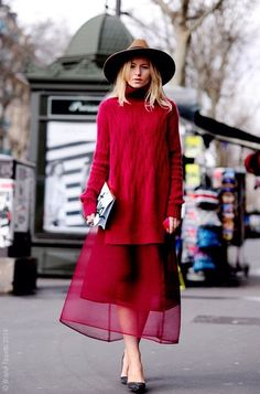 Red on Red. Long red oversized sweater over a  red skirt, which has a sheer organza layer.  Wide brim hat, tan. Simple black flats.