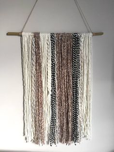Off-white beige and black handmade Boho style yarn wall art hanging. Will blend beautifully with any decor style. Great for baby shower gift/decor, college decor. Personalized gift for new home. Dimensions: Bamboo stick 21 in length with wool, poly and alpaca yarn. Yarn is 28 in length
