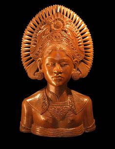 Dit borstbeeld stamt uit de jaren vijftig en stelt  Sri Dewih voor. Sri Dewi is een godin die al voor de komst van het Hindoeisme bekend was , maar ze werd hartelijk opgenomen in de uitgebreide familie van Hindoe goden en godheden. Ze is niet alleen de rijstgodin , maar ook die van de vruchtbaarheid. Dit beeld komt vaak alleen voor , maar komt ook wel voor als echtgenote van het bekende
