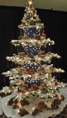 "Beautiful Christmas Display. Created from a regular Christmas tree, this "" antique paper house village"" tree was made by eliminating every 3rd row and bending the 2 remaining rows  to form a layer. Corrugated blue cardboard with lights punched  through, polyester batting snow, and tinsel icicles help finish the look."