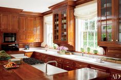 The kitchen of a Philadelphia home by designer Thomas Jayne features mahogany cabinetry inspired by 18th-century models and is outfitted with Miele ovens, a Viking cooktop, and Rohl sinks with Dornbracht fittings.
