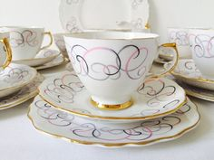 A clean and simple bone china tea set decorated with pink, black and grey swirls against the crisp white background and gilt details. The set is made up of 21 pieces, 6 teacups, 6 saucers, 6 tea plates, milk jug, sugar bowl and matching cake/serving plate all in excellent condition with little to no signs of use or wear. The base of each piece is marked Crown Regent, Bone China, Made in England and was produced during the 1960s in the Staffordshire area. A sweet, feminine tea set just…