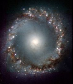 NASA's Spitzer Space Telescope has imaged this coiled galaxy with an eye-like object at its center. The 'eye' at the center of the galaxy is actually a monstrous black hole surrounded by a ring of stars. In this color-coded infrared view from Spitzer, the area around the invisible black hole is blue and the ring of stars, white. The galaxy, called NGC 1097 and located 50 million light-years away, is spiral-shaped like our Milky Way, with long, spindly arms of stars.