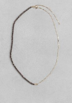 Dazzling faceted beads team up with a delicate shiny chain to form this eye-catching asymmetric necklace.