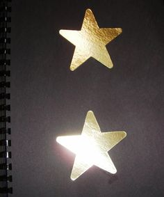 Two gold stars on black paper