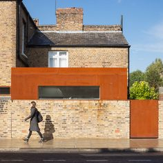 This oxidised-steel extension to an end-of-terrace Victorian house in east London peeks over the top of the adjacent brick boundary wall