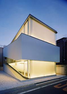 The C1 House, by Curiosity and Milligram Studio, is a glass box wrapped by a white, exterior walkway that elevates at a angle as it goes higher.
