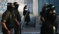 Una niña con su uniforme escolar mira a los miembros de las Brigadas Ezzedine al-Qassam, brazo armado de Hamas durante un mitin en la ciudad de Gaza, con motivo del 25 aniversario de su fundación. (AFP)