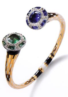 An Art Deco Egyptian-style bangle, by Cartier Paris, circa 1921. Platinum, gold, cushion-shaped sapphire, octagonal emerald, faceted and calibré sapphires and emeralds, old-cut diamonds and enamel. Cartier generally labelled this kind of bangle 'Egyptian', 'Sudanese' or 'Indian'.
