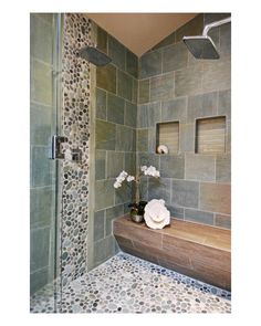 Wood does not perform well in moisture-prone areas, so a porcelain wood plank was used to re-create the warmth genuine wood offers. It's also used to create the spa look of a teak bench without the maintenance. And to enhance the spa feel, pebbles in the shower pan are like a daily massage on your feet.