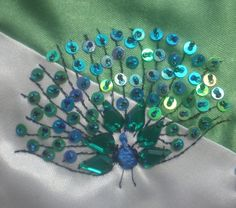 Peacock design--embroidery with sequins and beads --would be cute with tiny buttons, as well.