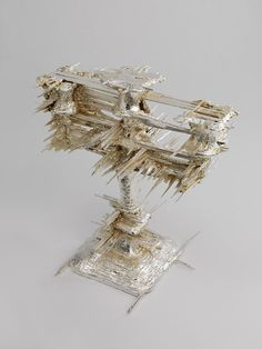 Candelabra, by Geoffrey Mann; made by scanning a silver candelabra with a 3-D scanner. the scanner couldn't tell the difference between the real surface and the spikes of light created by the reflection of its own lasers. the image file was then fed through a 3-D printer.