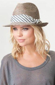 une fille blonde avec un chapeau beige de paille
