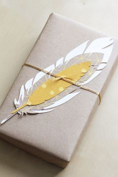 cut out feathers from scrapbook paper tied onto a brown paper wrapped package.