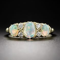 English 18k Opal and Diamond Ring. A classic Victorian design is perfectly emulated in this three-stone opal and diamond ring, recently crafted in England in rich 18K yellow gold. The enchanting trio displays a wide ranging palette of electric pastel colors with emphasis on green, blue and pink, further enlivened by two pairs of bright and sparkling European-cut diamonds