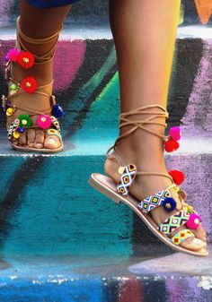 Go ahead - try to resist the urge to bust your best moves while wearing these beaded sandals. We dare you! Irresistibly detailed with colorful pom-poms, golden coin-shaped charms, and timeless ankle laces, these feisty flats transform every step into a full-on fiesta!