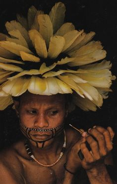 Intricacy in the making. / Trobriand Islander, adorned with cockatoo feathers, paints his face for a yam festival dance.