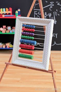 "DIY abacus. 1) Paint an open frame, dowel rods and wooden beads and wheels. Let dry. 3) Cut 4, 12"" pieces of a 3/16"" and 1/8"" dowel rod. 4) Using 1/8"" drill bit, drill 8 holes (4 on each side directly across) being sure to evenly space the holes. 5) Do the same for the other 8 holes, only with 3/16"" drill bit. 6) Slide all beads (by color) onto the 3/16"" dowel rods and all wheels onto the 1/8"" dowel rods. 7) Push the ends of all dowel rods into the appropriate holes. Use glue to secure."