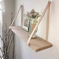 étagère originale en planche de bois suspendue par des lanières en cuir beige