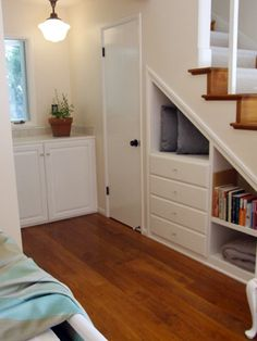 Create under stair storage for... and i just thought of this... SHOES!!  you could get them away from the front door altogether!!  just cut into the stair wall about a foot or so and give it block shelving so everyone can put their shoes in a hole when they come in!  i'm a genius...