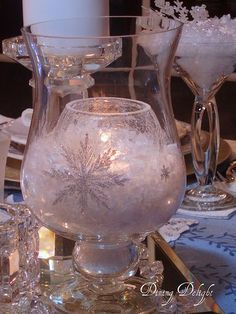This website has a nice crystal and white tablescape...you can DIY this hurricane...use glue and glitter to place snowflakes on outside (buy a stencil if you need a pattern), fill with snow, then place another candle globe inside...ck for flammability on snow...safest to use a bright battery candle