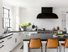 a bold black hood punctuates this black and white kitchen | house tour via coco kelley