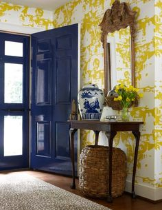 Yellow and blue foyer design with yellow chinoiserie wallpaper and glossy blue cobalt blue front door. Antique console table with cabriolet legs with Chinese ginger jar and woven basket. Antique wood mirror over foyer table. Decor, Small Entryways, Interior, Decor Inspiration, Home Decor, Yellow Wallpaper, House Interior, Interior Design, Entryway Style