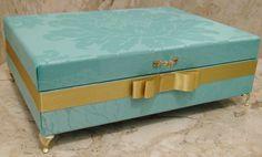 Caixa em MDF pintada ao fundo com tinta PVA para sua maior proteção. Revestida com tecido jacquard , cordão de São Francisco, laços e chatons pérola. Apliques em pezinhos e puxador em metal dourados.