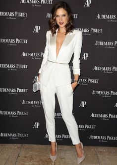 Alessandra Ambrosio wears a winter white suit with a metallic belt, nude suede heels, and a metallic clutch