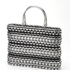 """This stylish 11 by 8 inch bag made of strips of soda pull tabs and tire inner tube was made by Mexico's BIO ImagineArte co-op, which takes the mantra of """"Reduce, Reuse, and Recycle"""" to heart.  The women are paid a fair price for each piece they make, which promotes the beauty of handmade products while addressing one of the main causes of environmental deterioration in Mexico– poverty. See more BIO ImagineArte products in our shop!"""