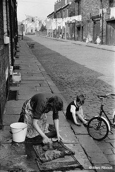 """Rug scrubbing"" may have been a pain, but car parking and litter wasn't..Leeds -1954..Photo by Marc Riboud, French photographer.."