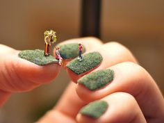 Here's an awesome little manicure, and we do mean little.  Alice Bartlett cut some pieces of green flocking to fit over her fingernails where she staged and photographed a series of scenes using miniature figurines to turn each green nail into its own little island.
