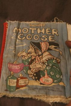 """Mother Goose, Rag Book 187, Dfan's Rag Book Co., LTD., """"Entirely British Manufacture"""", London. At work with her aromatic magical potions of Rhymes, adding from the bottles labelled """"Jokes"""", """"Fun"""" and """"Extract of Nonsense""""."""
