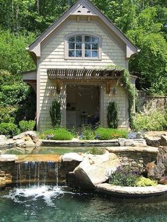 Stunning Relaxing Garden And Backyard Waterfalls: Small Two Storey White Wooden Cottage With Beautiful Man Made Swimming Pool Fountains Surrounded By Simple Green Garden Design ~ wetwillieblog.com Decorating Inspiration