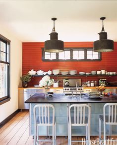 In this Long Island kitchen in a former camp cottage, designer Amanda Kyser chose Benjamin Moore's Merlot Red for one wall. It sets off white dishware salvaged from a grand seaside hotel in France that was torn down.