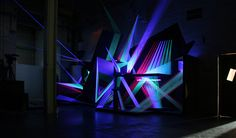 Post-industrial neon textile installation at the Red Bull Music Academy 2008, Barcelona.D98-4C is an interactive installation composed by a modular structure assembled through thread grids.The user can control different ultraviolet light points to bring…