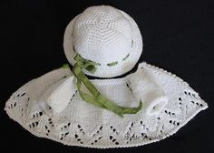 Smocked-Embroidered-Ensemble-for-Effner-13-Little-Darling-Dolls. The cardigan to this ensemble is knit of a soft silky bamboo yarn edged in a delicate lacey stitch. It closes in front with one tiny green button at the neckline. The hat is crocheted of the same bamboo yarn and is laced with a green silk ribbon.