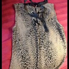 Leopard print tee. Cool  back on this cute tee. Short sleeve. Crisscross with black ribbon. Dress up or down. Use. Good condition. Tops