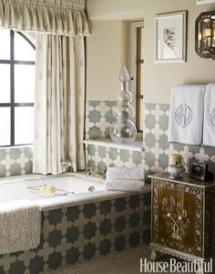 Tiled Bathroom: Designer Cathy Kincaid used Farrow & Ball's Old White paint on the walls has the same muted tone as Moroccan Cross and Star tiles by Ann Sacks. Curtains are Cowtan & Tout's Irina Sheer in Sky and Ivory. Indian inlaid cabinet from John Rosselli.