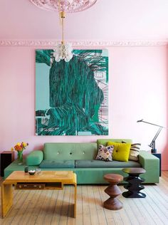 An eclectic living room featuring pale pink walls and ceiling and a green sofa.