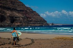 A surfer heads out