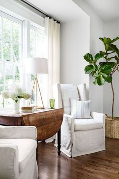 Pretty and practical slipcovered armchairs provide a welcoming spot to linger. The walls, coated in a custom shade of white, have a flat finish to create a more historic feel. Finishing the look: a rustic drop-leaf table—scored from a fruitful antiquing excursion—provides a visual break from the pristine palette.