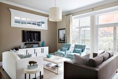 Designer Claire Paquin didn't scrimp on seating in this family-friendly living room. A pair of turquoise armchairs pair with a chocolate brown sofa to add a rich layer of color to the neutral palette. A sleek console table keeps a low profile below the mounted flat-screen TV and provides precious storage space.