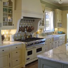 Happy yellow kitchen cabinets with marble counters and white 48 inch stove. Love the pot rack hanging just below the vent hood. Nice corbels there too.