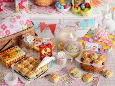 Ideal for Easter baking, this hot cross buns set includes a pan of hot cross buns fresh from the oven, glass bowl of powdered sugar glaze for piping, glass measuring cup of flour, large box of baking raisins, yellow ceramic bowl with raised dough, bunny sign and basket of hot cross buns. A split hot cross bun with butter on it completes this set.  PLEASE NOTE: Bunny sign is not attached to basket. Buns are attached to baking pan, basket and plate. Buns in front of basket are also included…