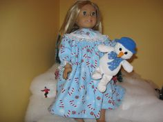 This is an adorable nightgown for the American Girl and other 18 dolls. It is made of 100% cotton flannel and the candy canes are on a light blue background. The nightgown is embellished with lace around the sleeves and the upper bodice and it comes with a darling little stuffed animal for your little doll to take to bed with.