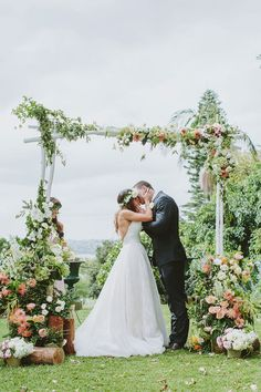 wedding ceremony kiss - photo by I Love Wednesdays http://ruffledblog.com/flower-filled-bohemian-australian-wedding #floralarch #weddingideas #ceremonies