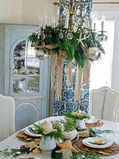 This dining room features beach vacation finds turned into a shell-themed Christmas table setting. Breezy fabrics, woven textures and seashells work well with evergreens, mercury glass and elegant china.