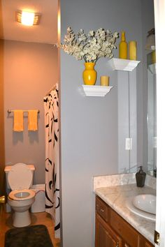 My newly decorated, gray and yellow bathroom.                                          Shower Curtain, soap pump and Rugs - Target ..... Wall Color - Smooth Pebble (lowes) ..... White shelves - Target ..... Things on the shelves - spray painted yellow vase, scotch bottle, candle                 ..... Towels - Walmart